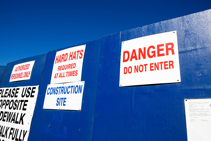 warning signs on fence outside construction area